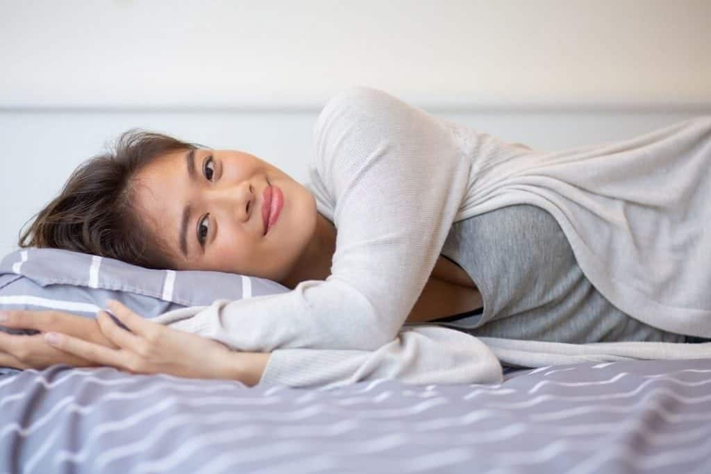 Woman in bed looking for the best mattresses for hot sleepers