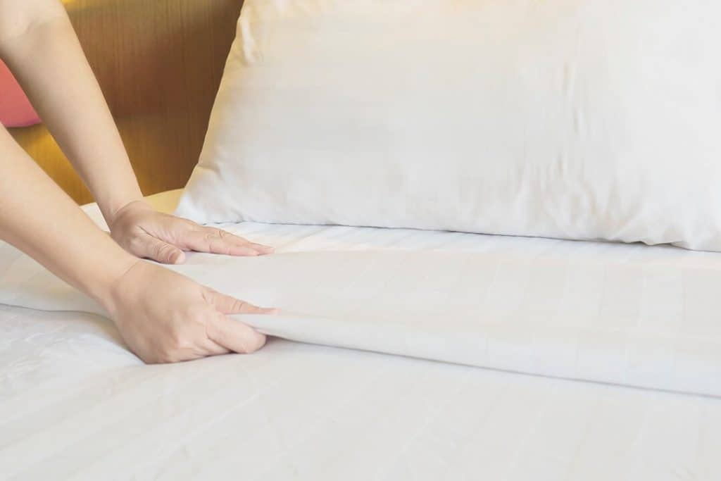 Woman cleaning the bed, finding the right sheets and to find the right pillow