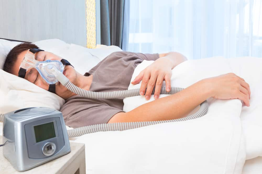 Man sleeping with CPAP to prevent snoring
