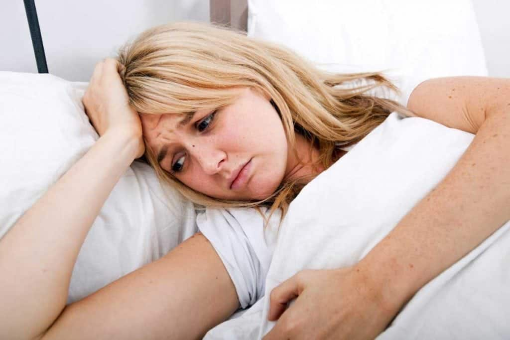 Young woman suffering from headache in bed