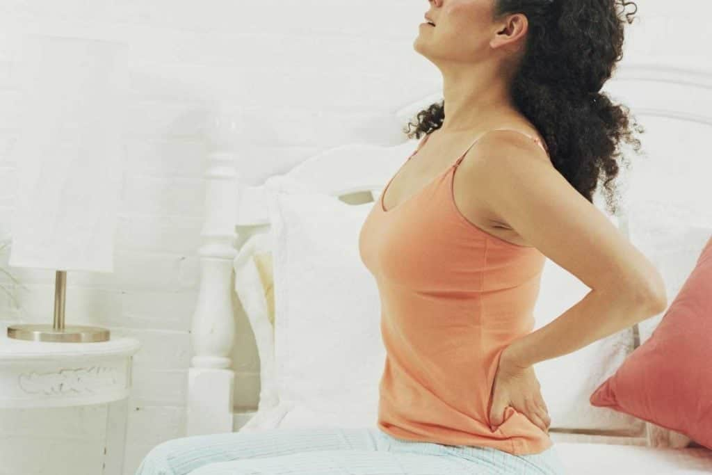Woman getting up on bed with back pain