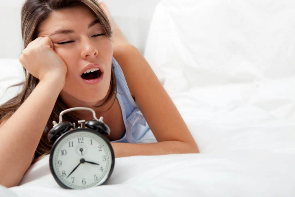 woman yawning in bed with alarm clock due to sleeping poorly at night