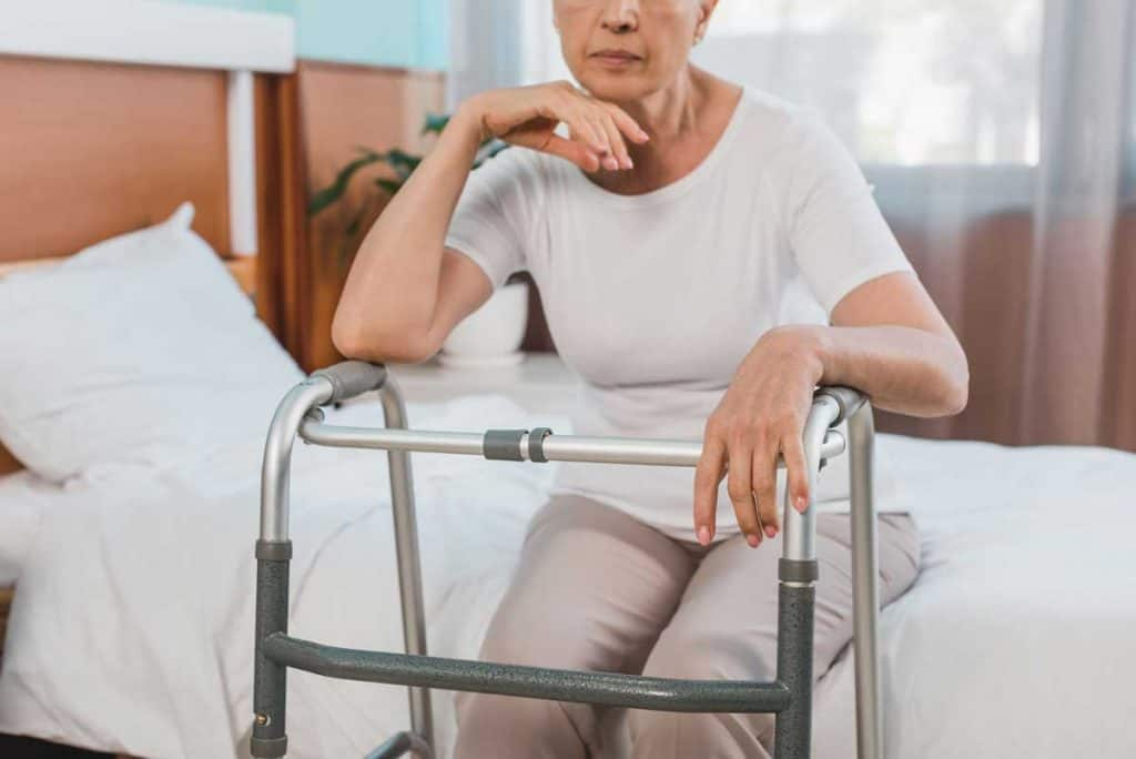 Woman and people living with disability in bed suffering from physical pain with walker