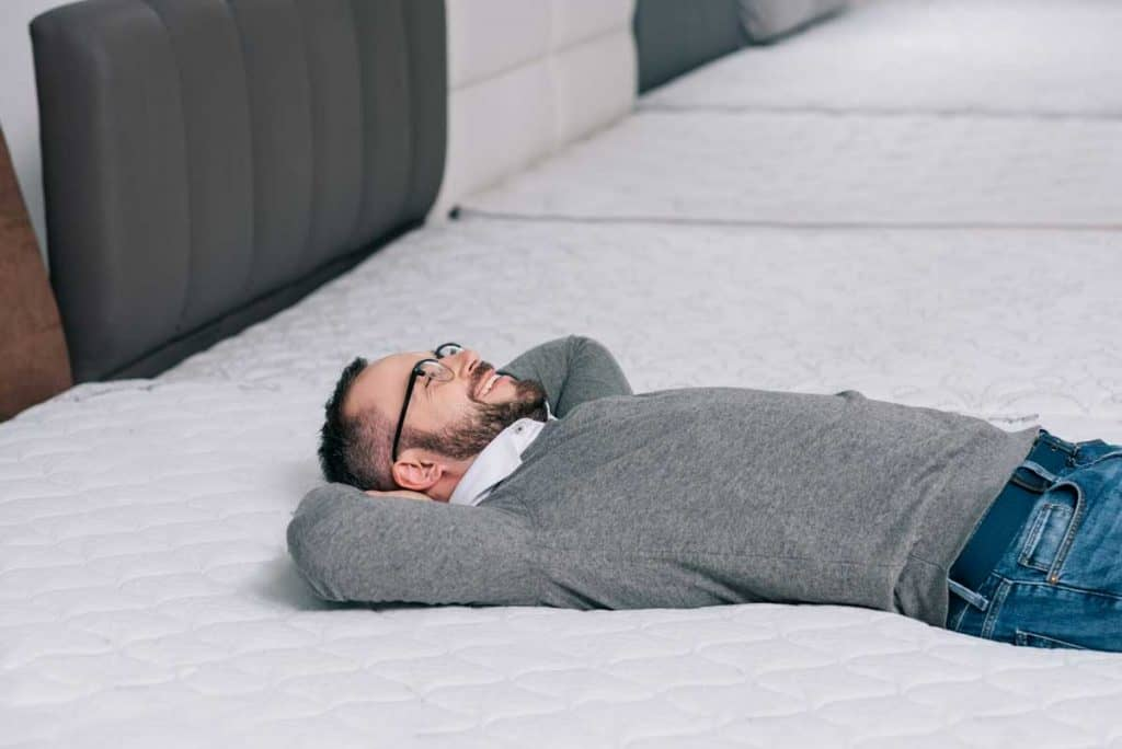 man lying down on mattress at a store