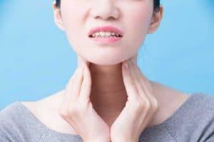woman rubbing irritated neck