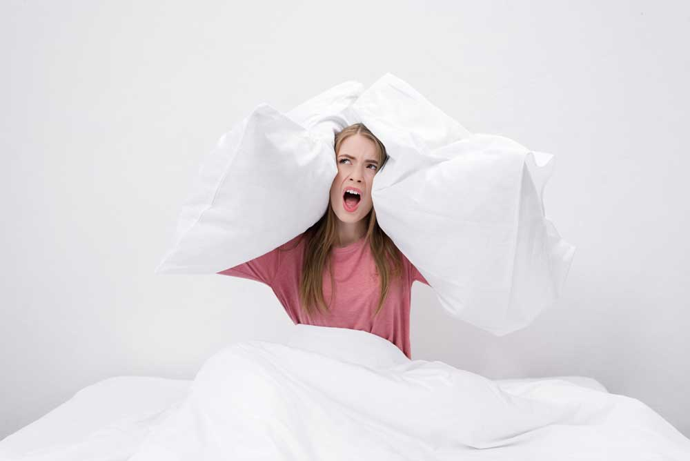 woman in bed holding pillows to her ears