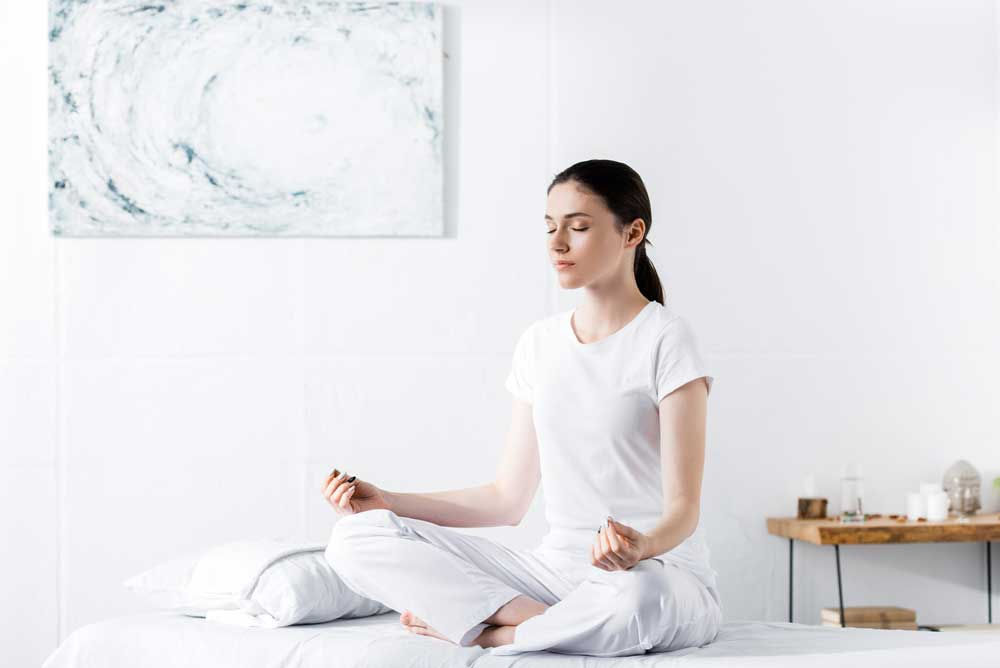 woman meditating in bed to overcome distractions when you sleep