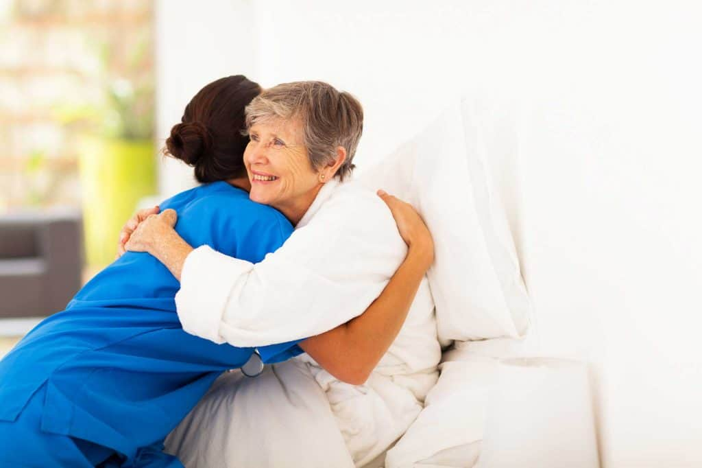 elderly woman giving a hug to home carer