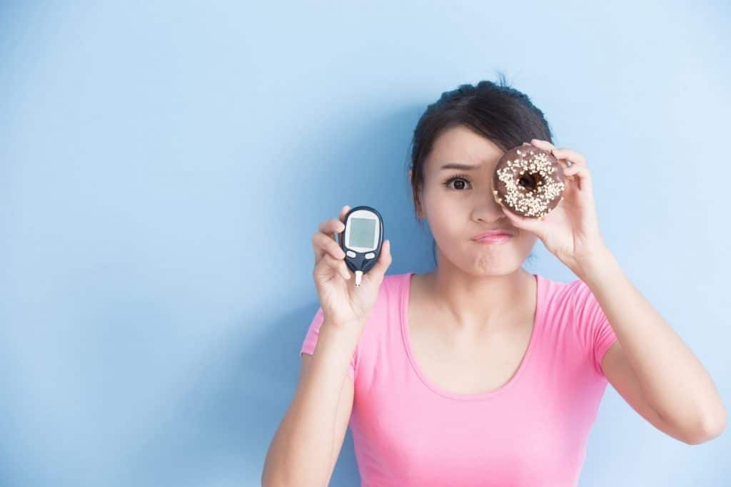 Woman holding a donut and blood sugar meter
