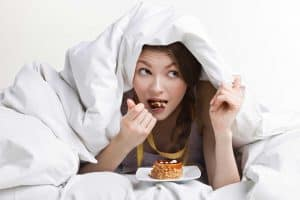 woman eating cake under bed covers