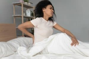 woman waking with fibromyalgia in bed