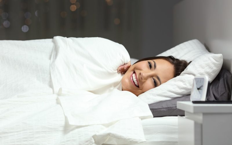 Happy woman covering with a blanket in the bed looking at camera in the night at home